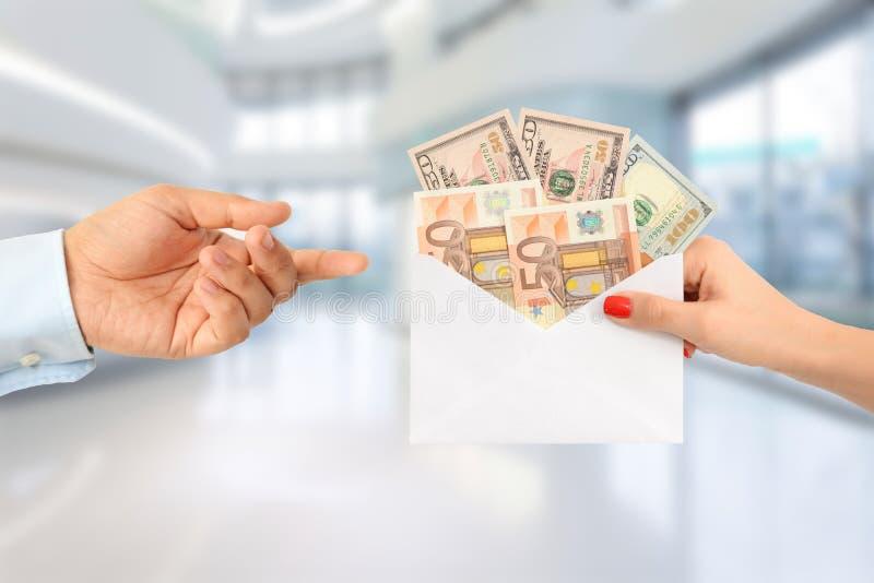 Kvinna som muter en man med ett kuvert som är fullt av pengar som föreslår en korrumperad vårdsystem arkivfoto