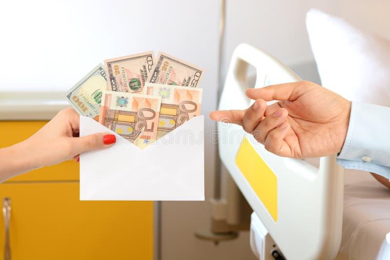Kvinna som muter en man med ett kuvert som är fullt av pengar som föreslår en korrumperad vårdsystem royaltyfri bild