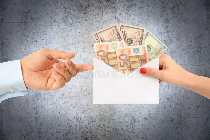 Kvinna som muter en man med ett kuvert som är fullt av pengar som föreslår ett korrumperat system royaltyfri fotografi