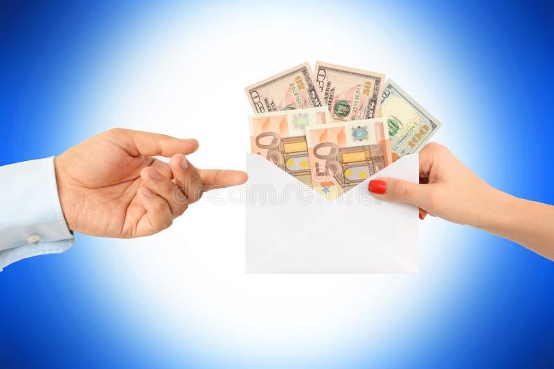 Kvinna som muter en man med ett kuvert som är fullt av pengar som föreslår ett korrumperat system arkivbilder