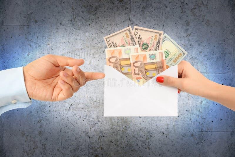 Kvinna som muter en man med ett kuvert som är fullt av pengar som föreslår ett korrumperat system royaltyfria foton