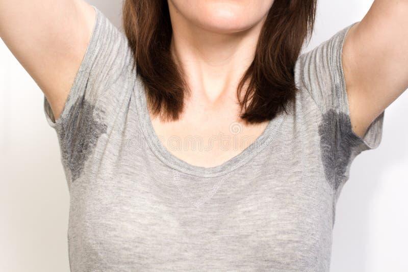 Kvinna som mycket dåligt svettas under armhålan royaltyfri fotografi
