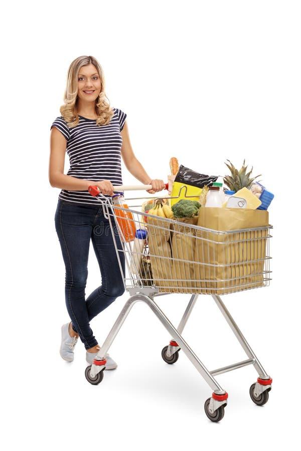 Kvinna som mycket poserar med shoppingvagnen av livsmedel royaltyfria foton