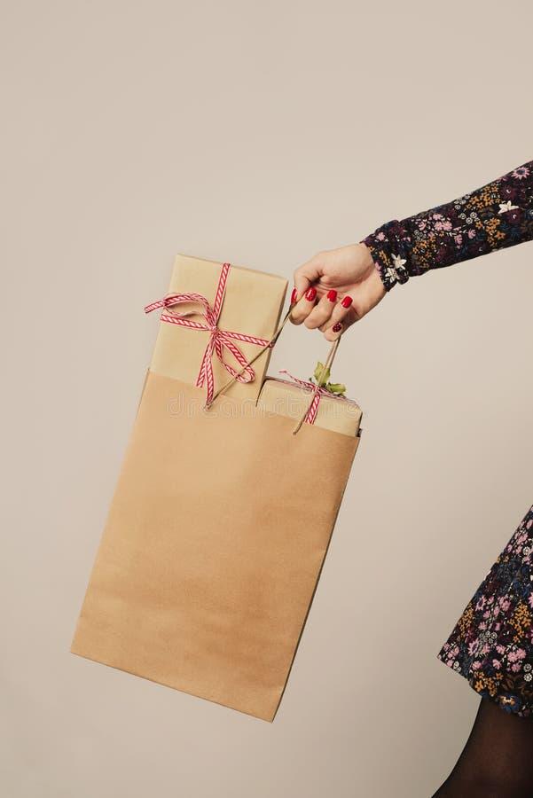 kvinna som mycket rymmer en pappers- shoppa påse av gåvor arkivbilder