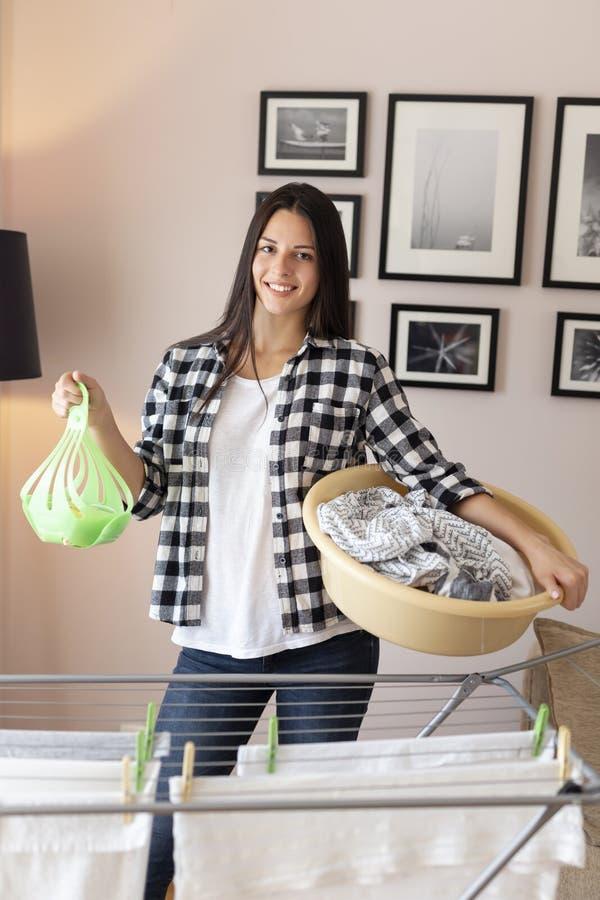 Kvinna som mycket rymmer en tvättbalja av våt kläder royaltyfria bilder