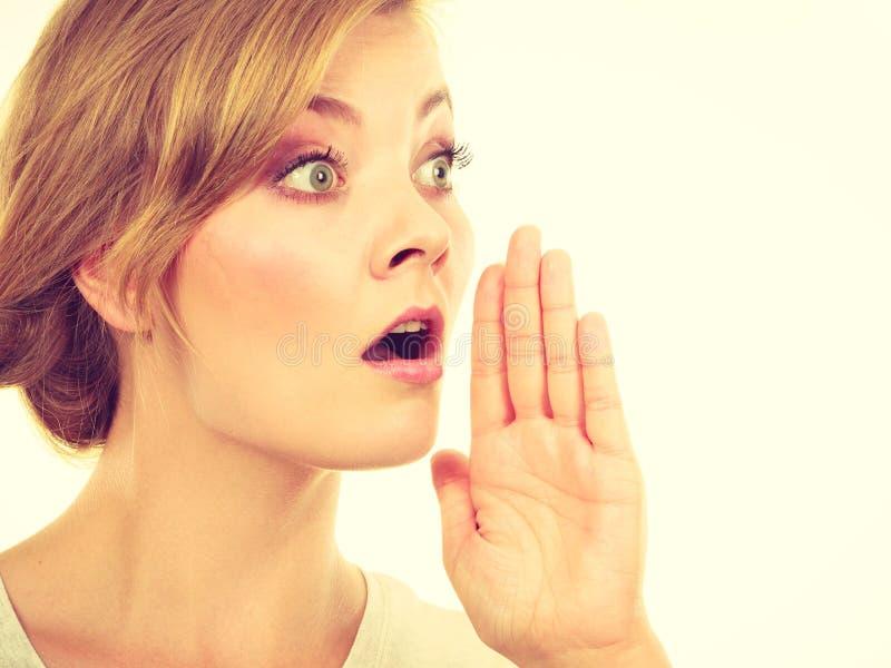 Kvinna som nästan viskar med munnen för hand royaltyfria foton