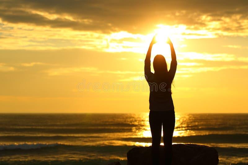 Kvinna som når solen på solnedgången på stranden royaltyfri bild