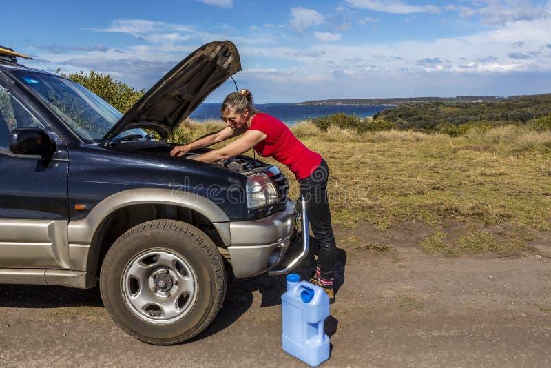 Kvinna som ner fixar hennes brutna bil 4wd royaltyfri fotografi