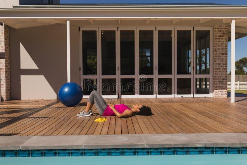 Kvinna som ner ligger i trädgården av hemmet efter en genomkörare arkivfoto