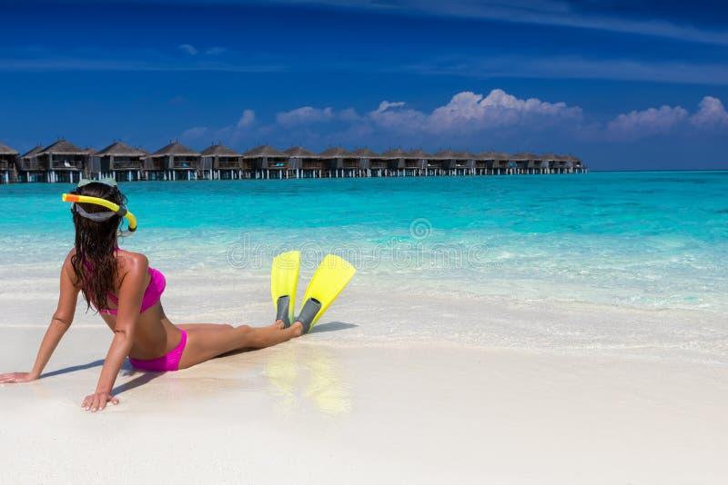 Kvinna som ner ligger med att snorkla flipper och maskeringen på en tropisk strand royaltyfri bild