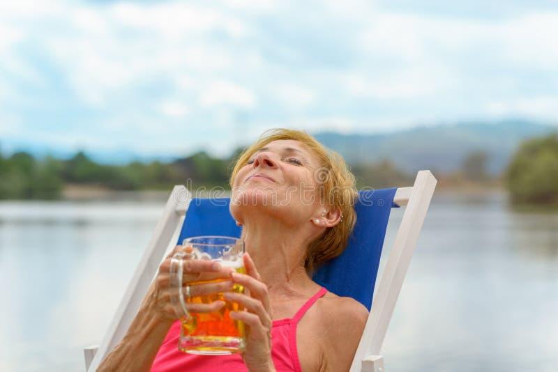 Kvinna som njuter av en halv liter av kallt öl arkivfoto