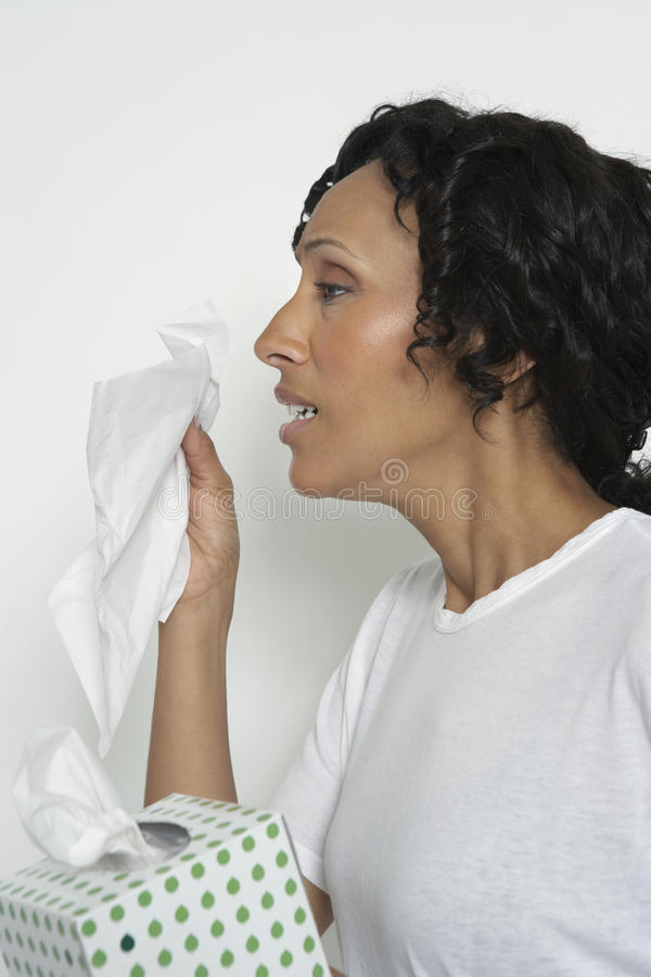 Kvinna som nyser in i silkespapper arkivbilder