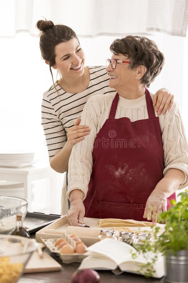 Kvinna som omfamnar hennes mormor arkivfoto