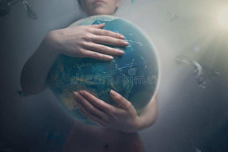 Kvinna som omfamnar jordklotet av planetjord Begreppet av att bevara miljön och förälskelsen för din planet Ton och loght arkivbild