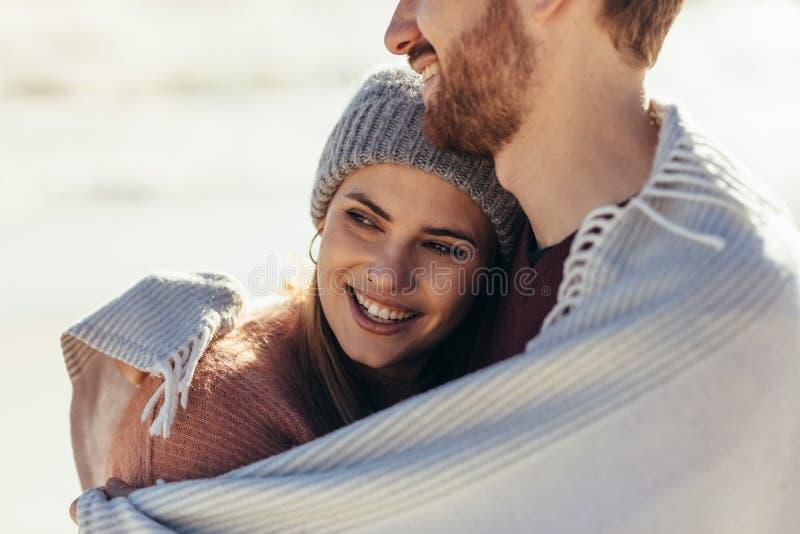 Kvinna som omfamnas av hennes pojkvän på stranden royaltyfria bilder