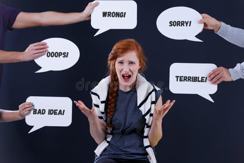 Kvinna som omges av kommentarer i anförandebubblor arkivbild