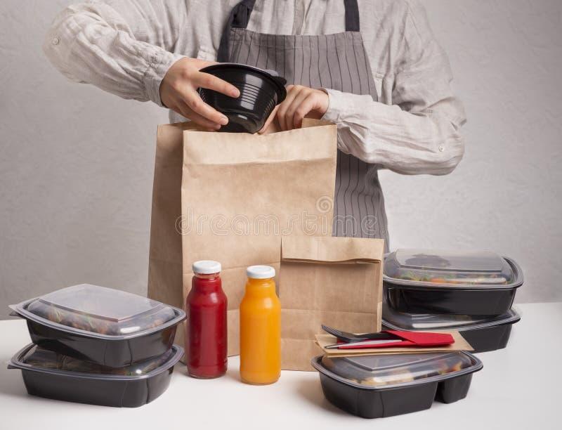 Kvinna som packar online-beställning av sunda mat- och detoxdrinkar royaltyfri fotografi