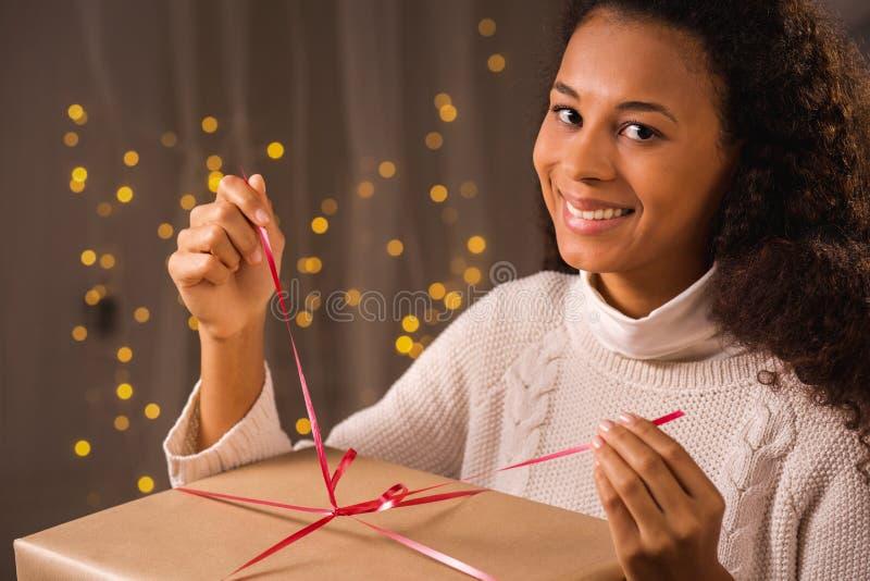 Kvinna som packar upp julgåva fotografering för bildbyråer