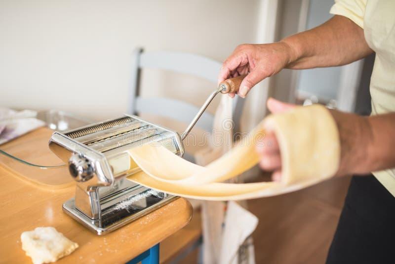 Kvinna som passerar ett pastaark till och med en maskin arkivfoto