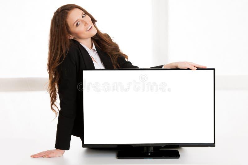 Kvinna som pekar blankotelevisionskärm med cipy utrymme för extra text eller diagram arkivbild