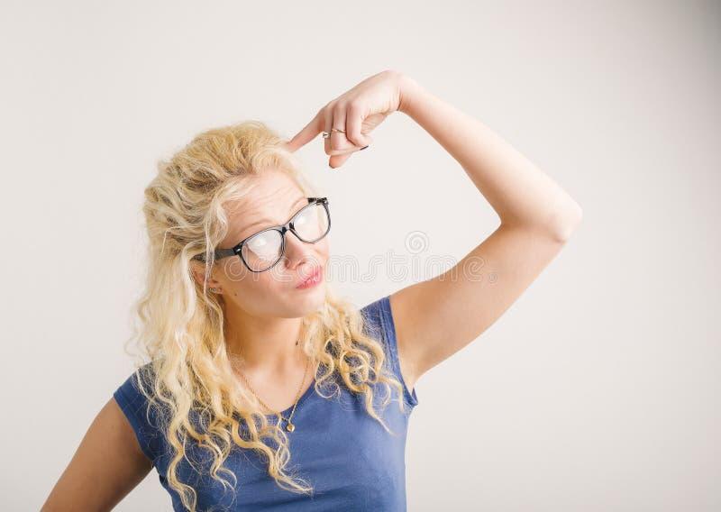 Kvinna som pekar hennes finger på hennes huvud arkivbilder