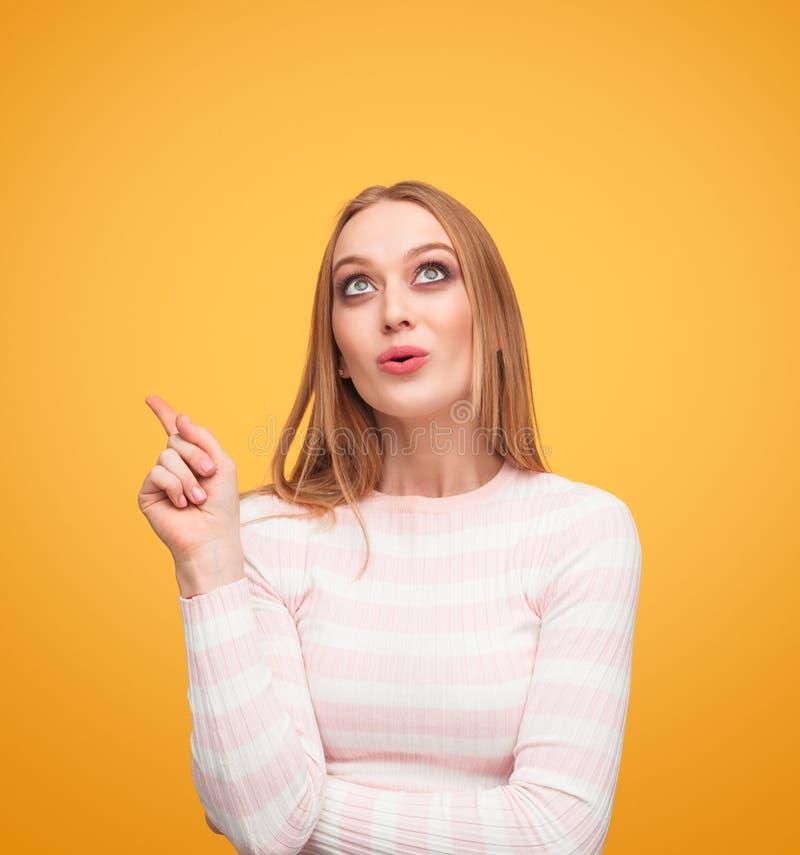 Kvinna som pekar och ser upp i studio royaltyfri bild