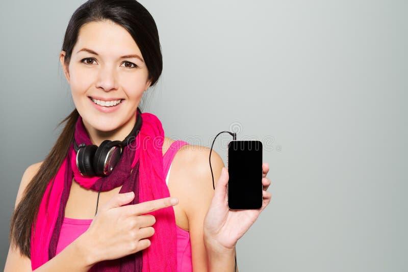 Kvinna som pekar till hennes smarta mobiltelefon royaltyfri bild