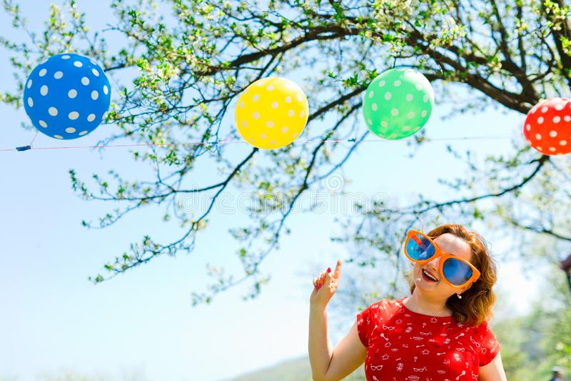 Kvinna som poserar i den röda klänningen och stora roliga solexponeringsglas på trädgård - ballonger royaltyfria bilder