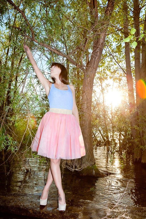 Kvinna som poserar i kjol och överkant på bakgrund av inställningssolen vid vatten fotografering för bildbyråer