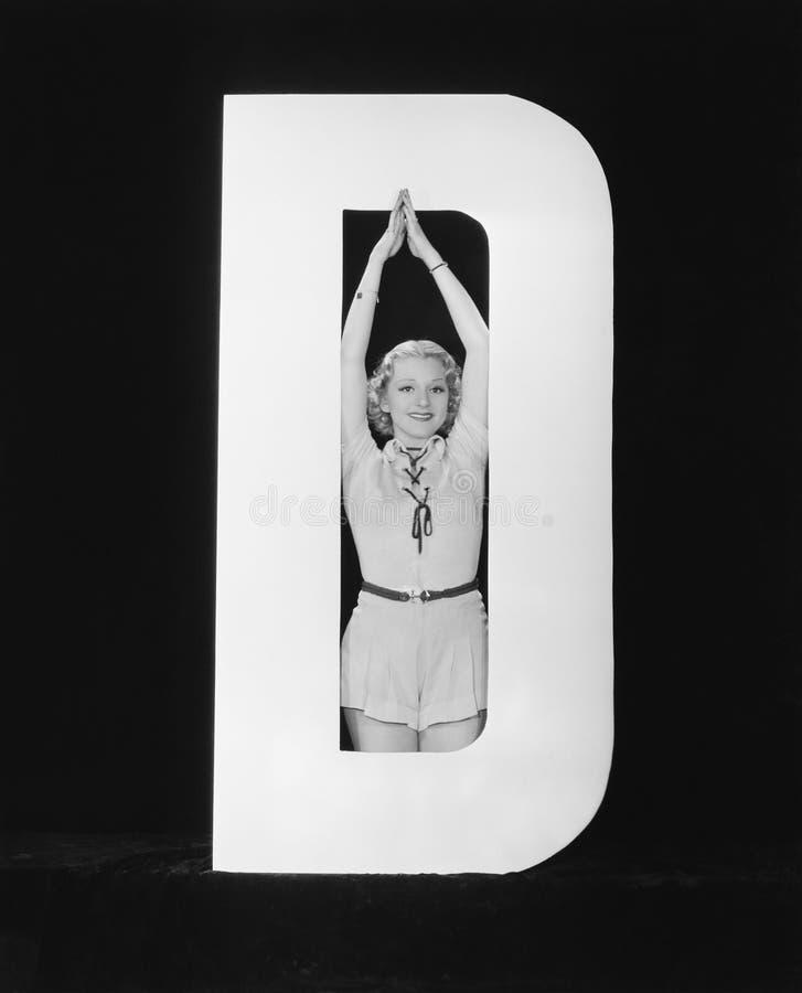 Kvinna som poserar i mitt av bokstav D (alla visade personer inte är längre uppehälle, och inget gods finns Leverantörgarantier s royaltyfria foton