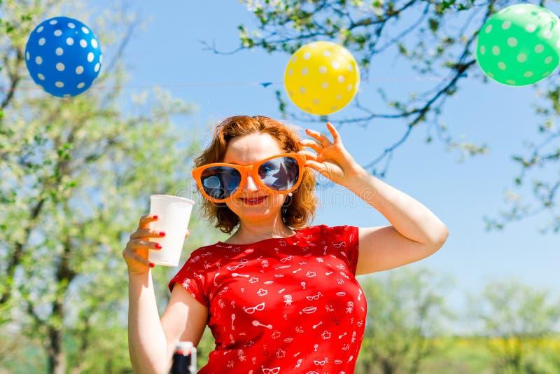 Kvinna som poserar i r?d kl?nning och stora roliga solexponeringsglas p? tr?dg?rdpartiet - sommarpicknick arkivfoto