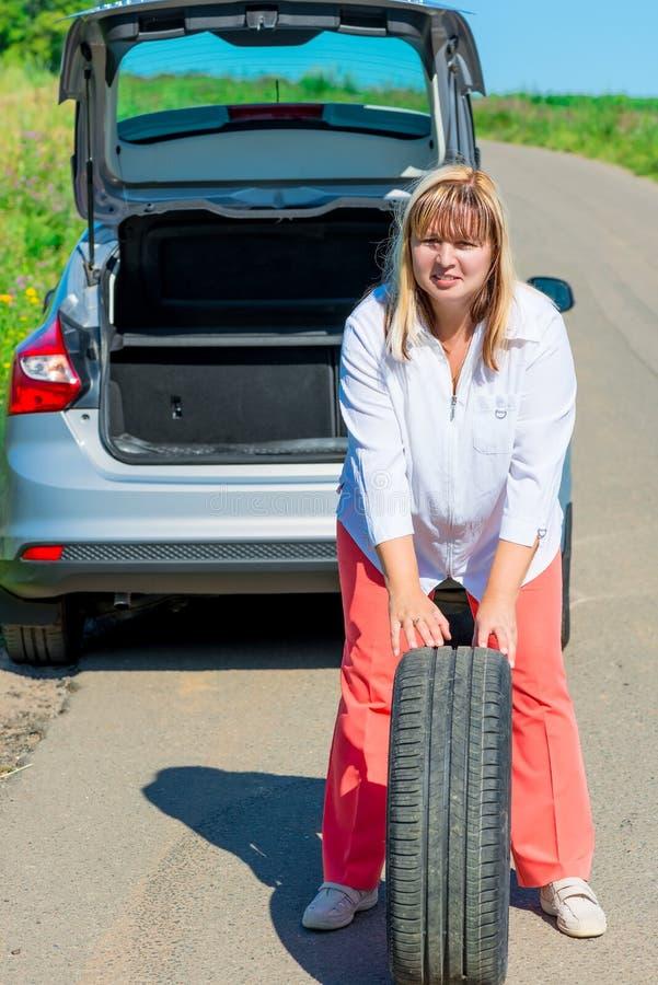Kvinna som poserar med ett extra- hjul nära bilen royaltyfri foto