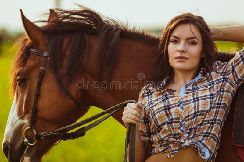 Kvinna som poserar med hästen arkivbild