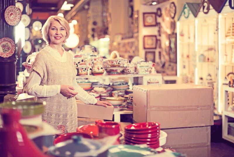 Kvinna som poserar med keramisk bordsservis arkivbild