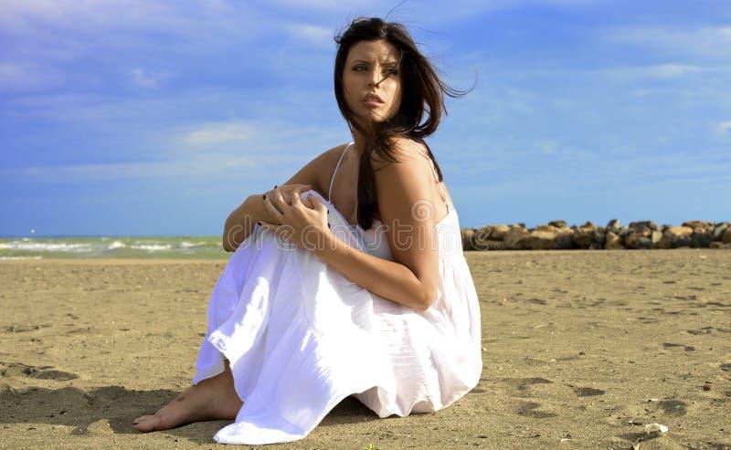 Kvinna som poserar med stormen som kommer på stranden royaltyfria bilder