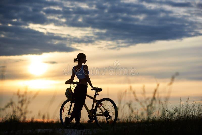 Kvinna som poserar nära cykeln och den enoying naturen fotografering för bildbyråer