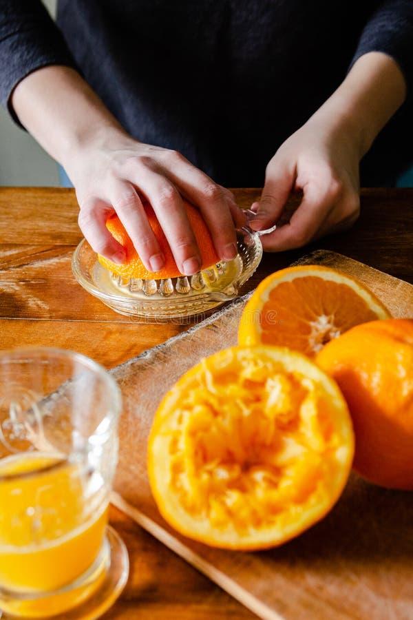 Kvinna som pressar apelsiner för ny fruktsaft royaltyfri bild