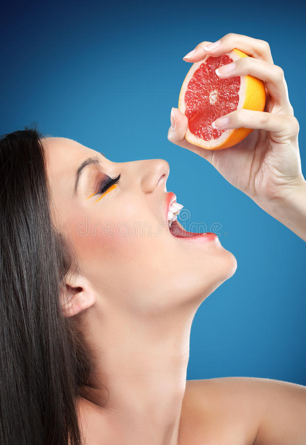 Kvinna som pressar orangen in i mun royaltyfria bilder
