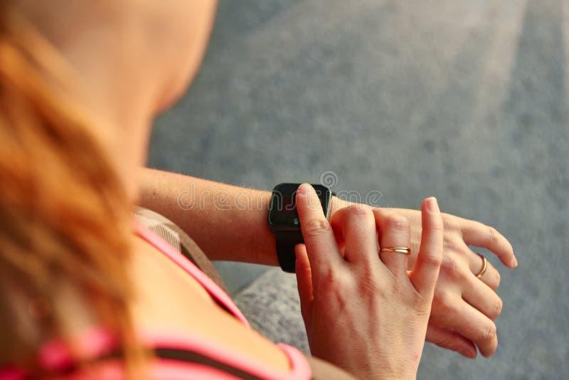 Kvinna som programmerar hennes smartwatch för gående jogga som spårar kapacitet royaltyfri fotografi