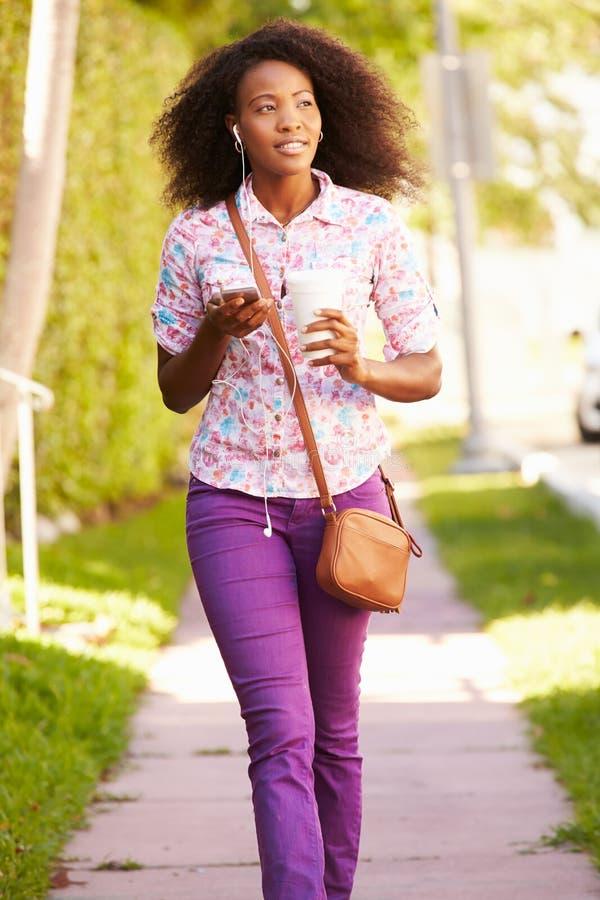 Kvinna som promenerar gatan för att arbeta att lyssna till musik royaltyfri foto