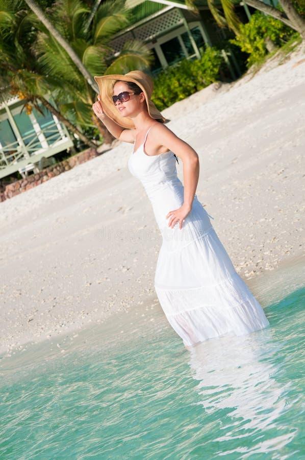 Kvinna som promenerar sjösidan på den tropiska stranden arkivfoto
