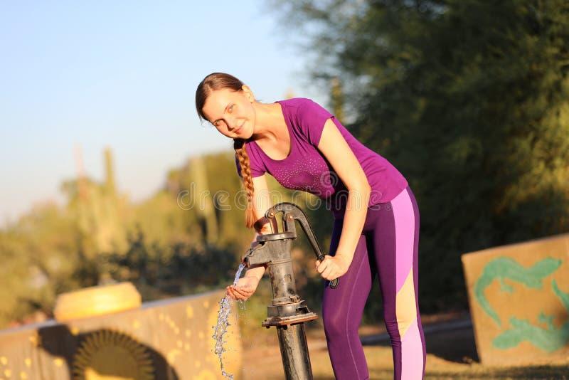 Kvinna som pumpar en brunn royaltyfri foto
