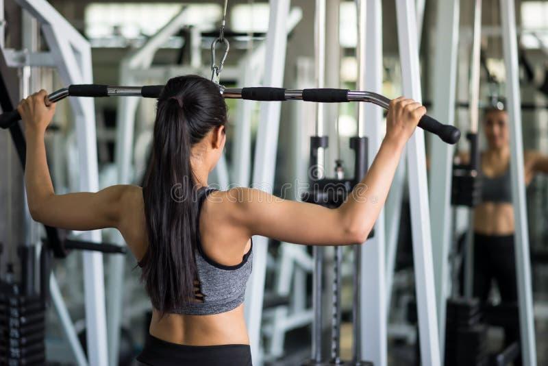 Kvinna som pumpar tillbaka muskler i idrottshall royaltyfri bild