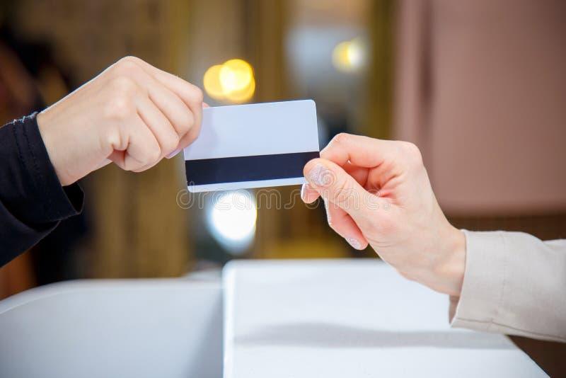 Kvinna som räcker över kreditkort på kassaapparaten royaltyfria foton