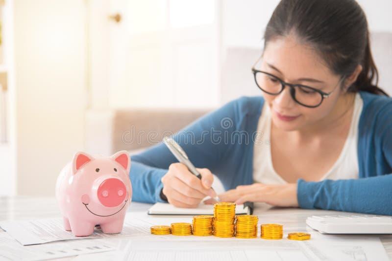 Kvinna som räknar och antecknar hennes besparingar royaltyfria foton