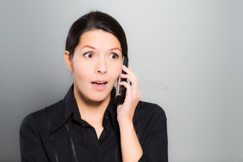 Kvinna som reagerar i häpnad till nyheterna på hennes mobil arkivfoto