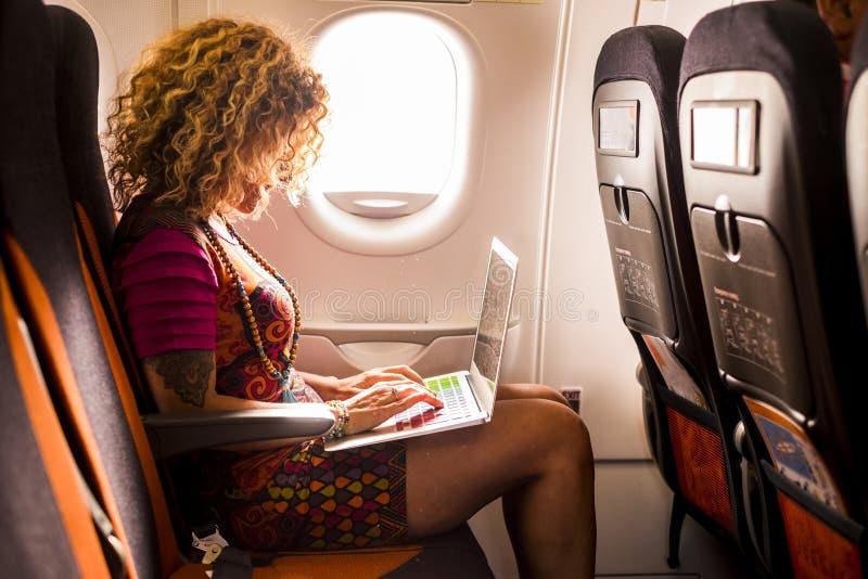 Kvinna som reser på flygplanflyget och ombord arbetar på en bärbar dator med ny teknik för internet för flygplan - folkförälskels royaltyfri bild