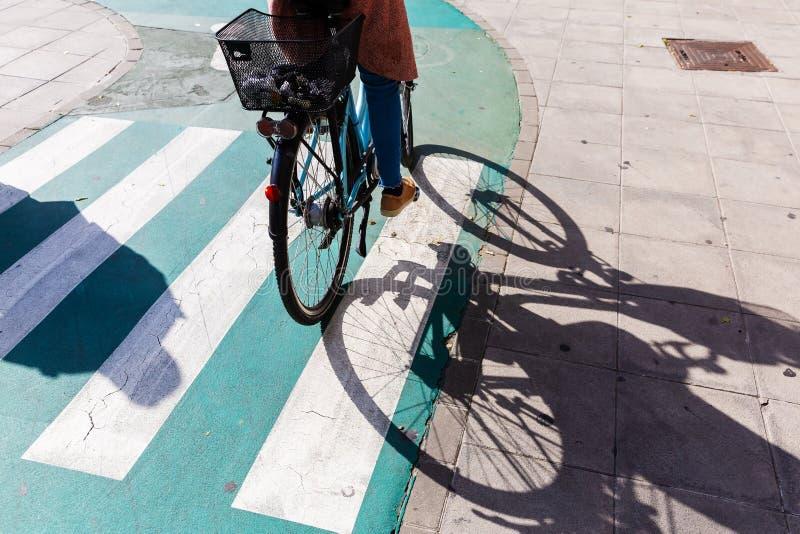 Kvinna som rider en cykel i staden royaltyfri foto