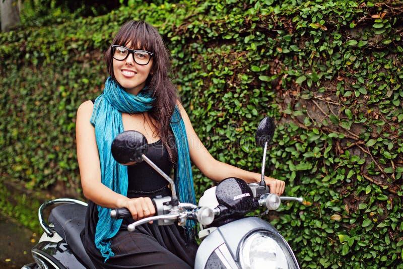 Kvinna som rider en moped arkivfoto