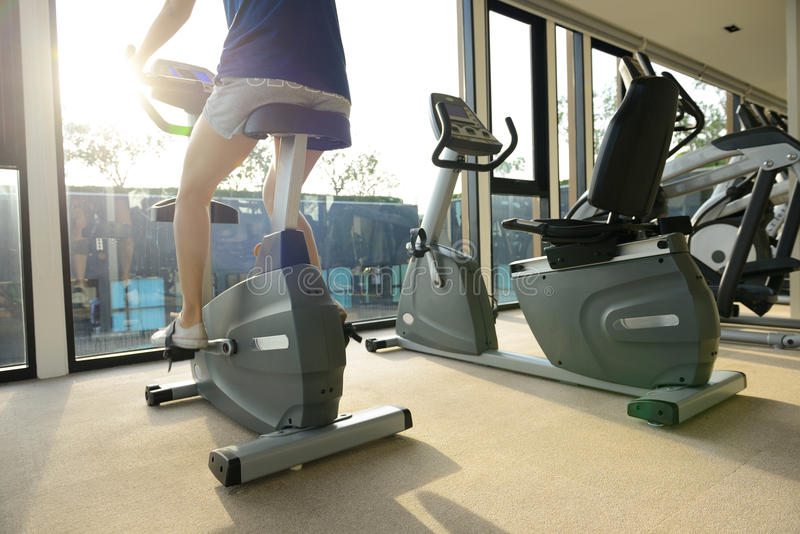 Kvinna som rider en motionscykel i idrottshall i morgonsolljuset royaltyfri foto